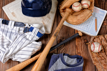 Overhead view of baseball gear on a rustic wood surface