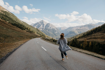 Switzerland, Engadin, rear view of woman walking on mountain road