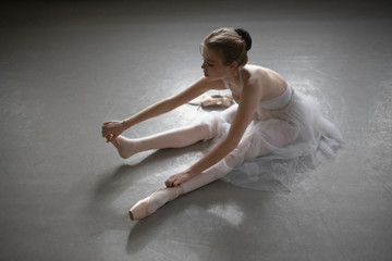 High angle view of ballet dancer sitting on floor in studio