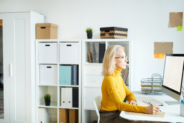 Side view portrait of elegant mature businesswoman working with computer while sitting at desk in office, copy space