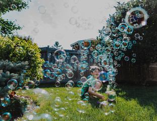 Smiling boy looking at soap bubbles in backyard