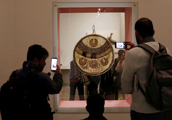 Journalists and photographers take pictures of a chimalli during a media tour as Mexico's National History Museum at Chapultepec Castle opens an exhibit showcasing the chimalli, or Aztec Shield, in Mexico City