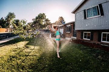 Happy girl wearing swimwear dancing on grassy field against clear sky in yard