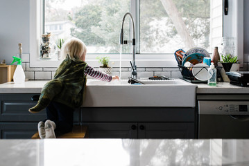 Rear view of girl washing hands in kitchen sink while kneeling on stool at home
