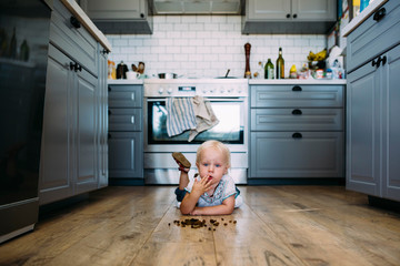 Cute thoughtful girl eating food while lying on hardwood floor in kitchen at home