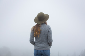 Rear view of woman standing in Yellowstone National park during foggy weather