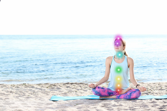 Young woman doing yoga exercises on beach in morning