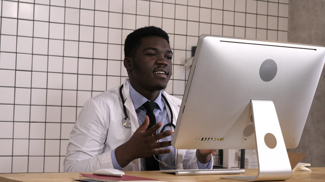 African male doctor having video conference on his computer.