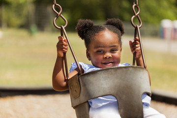 Cute little African American swinging at the park.
