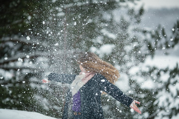 Funny girl playing with snow in an amazing winter's park.