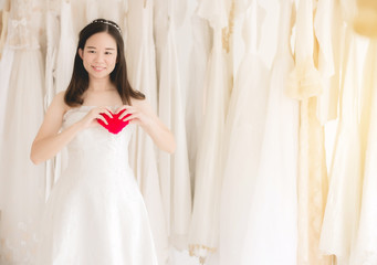 Young beautiful asian bride women in white dress with hand holding model heart red color,Happy and smiling
