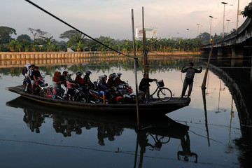 Motorists are being transported on a raft as they cross a river in Jakarta