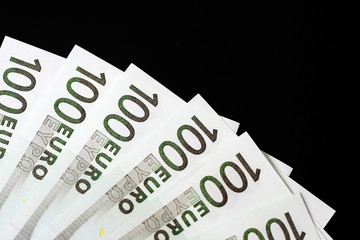 One Hundred euro banknotes on a dark background close up