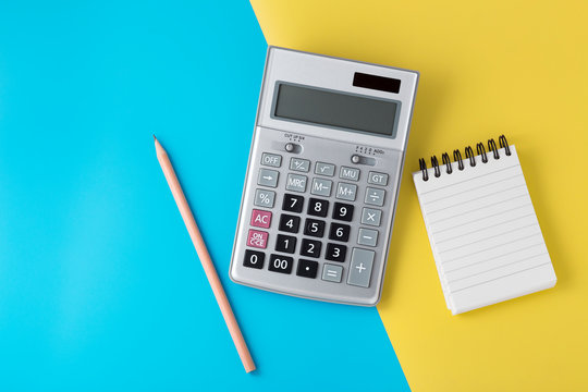 Calculator and notepad on light blue and yellow background