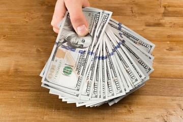 hand, money dollars usa - Image on wooden background.