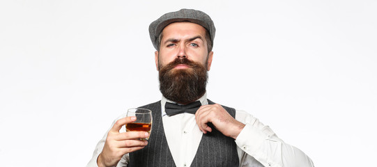 Brutal bearded man with glass of whiskey, brandy, cognac. Attractive man with a cognac. Old hipster style. Whiskey, brandy, cognac drink. Fototapete