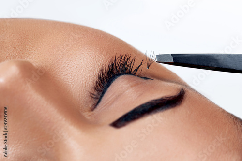 2c77cf32077 Beautiful Woman with long eyelashes in a beauty salon. Eyelash extension  procedure. Lashes close up.