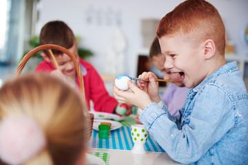 Screaming boy painting easter egg