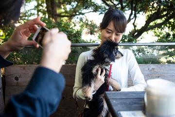 飼い犬と仲良くカフェのテラスでランチをするカップル