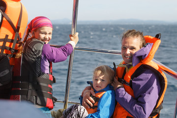 Family on a blue whale watching trip. Smiling girl in safety jacket on a boat trip. Mother holding baby..