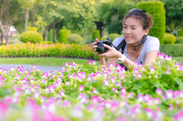 Female photograph with camera taking a picture of flower