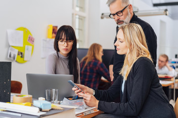Woman with smartphone in office scene