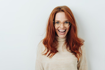 Excited redhead woman wearing glasses