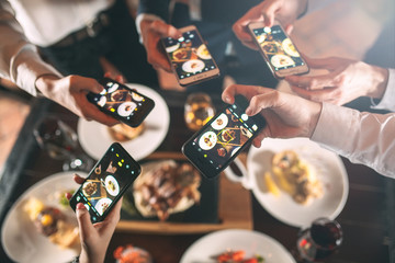 Group of friends going out and taking a photo of food together with mobile phone