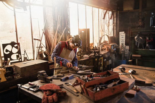 A female craftsman in her workshop working on a metal piece