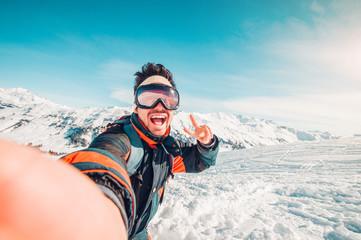 Happy handsome man taking a selfie hiking
