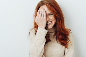Smiling attractive woman covering one eye