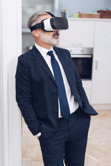 Mature man with VR goggles oh his head