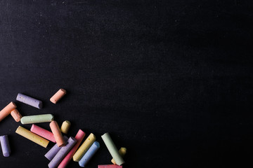 Multicolored crayons lie on a black chalkboard, copy space. The concept of school, education and childhood.