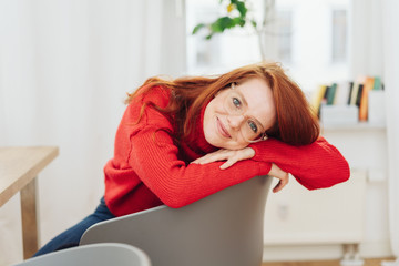 Smiling young woman relaxing in an armchair
