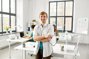 business and people concept - happy smiling man with glasses at office