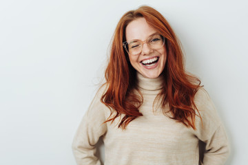 Laughing red-haired girl in glasses portrait