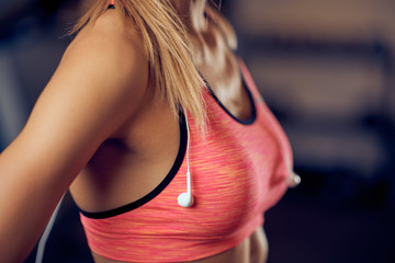 Close up of woman's breasts in sport top. Around neck earphones. Gym interior, healthy lifestyle concept.