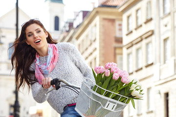 stylish woman in gray hat on a bicycle