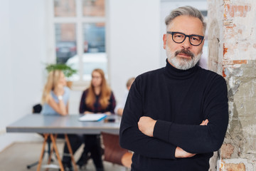 Confident mature grey-haired man in office