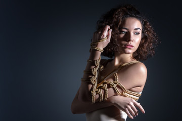 Beautiful fashion brunette woman with tied chest and hand with decorative knots of natural jute ropes. Ancient Japanese art of aesthetic bandage and tying shibari kinbaku. Sexual underwear concept.