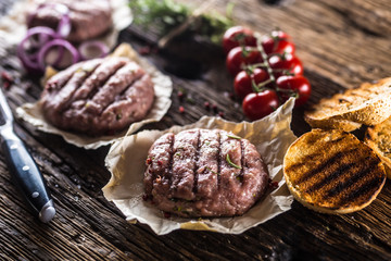 Raw burgers on wooden table with onion tomatoes herbs and spices