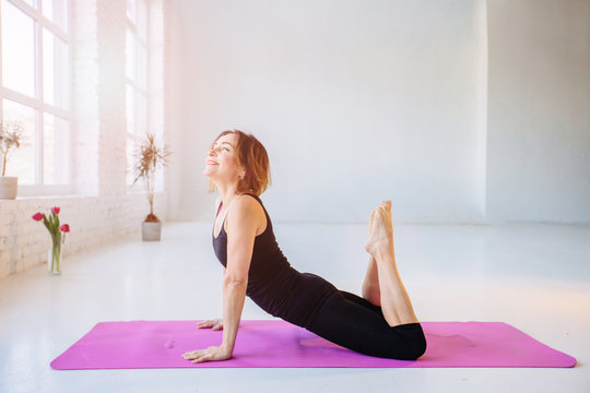 Mature slim strong woman while doing yoga pilates stretching relaxation exercise in white loft studio interior. Breathing, concentrating, healthy lifestyle concept.