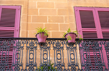 Flower pots on a balcony, shutters on the windows