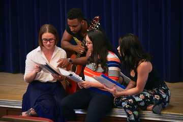 Multi-ethnic students reading music sheets on stage in auditorium