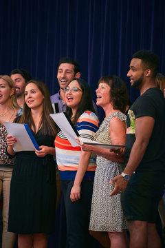 Multi-ethnic people singing in choir on school stage
