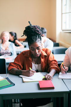 Young woman with dreadlocks writing in classroom