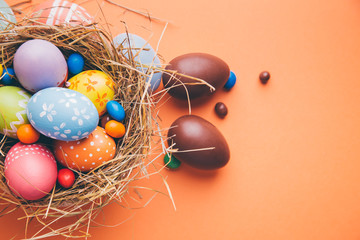 Colorful easter eggs with chocolate and candies in a nest on a orange background