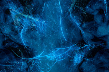 Mysterious texture abstraction cracked glass behind which mystical blue steam