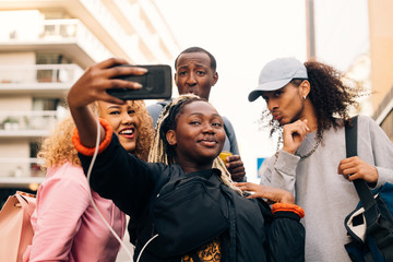 Low angle view of teenage girl taking selfie with friends on smart phone in city