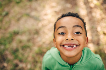 High angle view of smiling boy with gap toothed in park